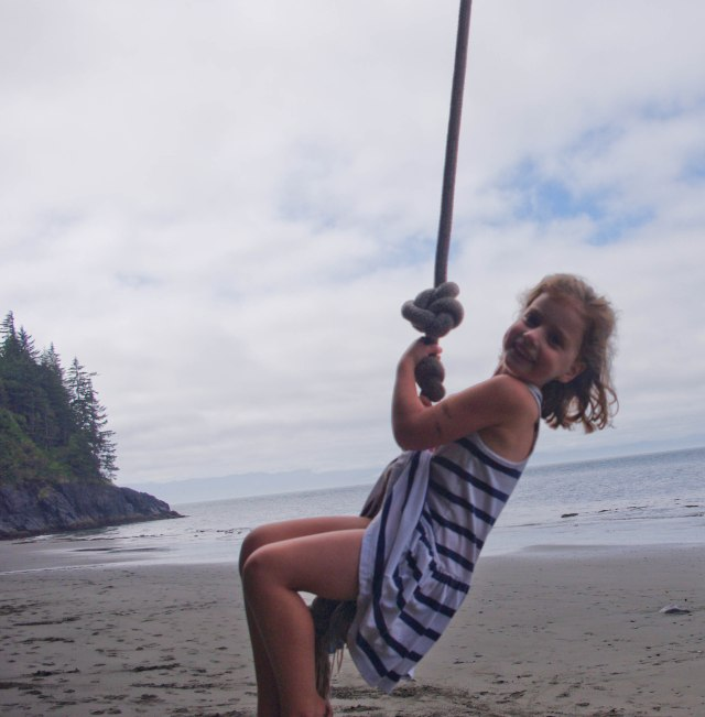 Rina, swinging from the rope swing on the beach