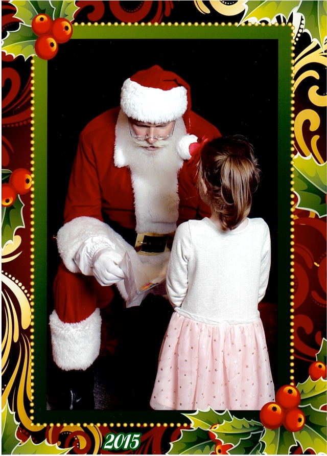 Rina, handing Santa a drawing she had done